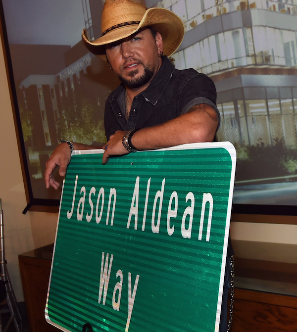 """MACON, GA - AUGUST 11:  Singer/Songwriter Jason Aldean with signage for """"Jason Aldean Way"""" at The Medical Center, Navicent Health's Eversole Auditorium on August 11, 2017 in Macon, Georgia.  (Photo by Rick Diamond/Getty Images)"""